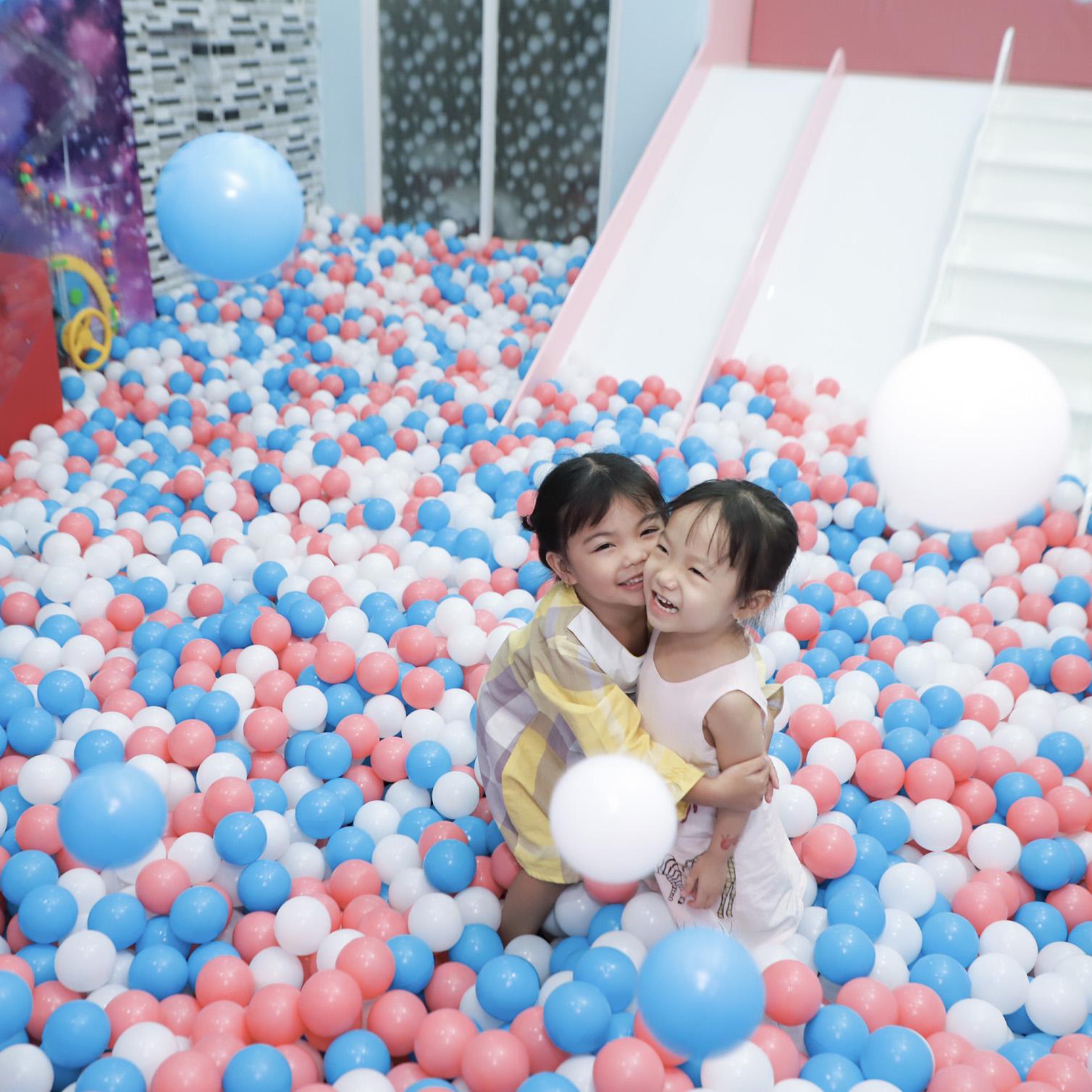 Hai bé gái đang chơi đùa trong bể bóng màu pastel